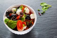 Caprese沙拉、小无盐干酪乳酪、新鲜的绿色叶子、黑橄榄和西红柿在白色葡萄酒在石backgr滚保龄球 免版税库存照片