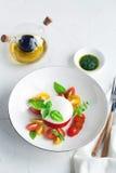 Caprese沙拉用成熟西红柿和无盐干酪乳酪与在白色背景隔绝的新鲜的蓬蒿叶子 免版税库存照片