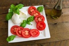 Caprese沙拉用蕃茄和无盐干酪在板材 库存照片