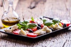 caprese沙拉 地中海沙拉 无盐干酪西红柿蓬蒿和橄榄油在老橡木桌上 carpaccio烹调非常好的食物意大利生活方式豪华 免版税图库摄影