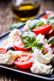 caprese沙拉 地中海沙拉 无盐干酪西红柿蓬蒿和橄榄油在老橡木桌上 carpaccio烹调非常好的食物意大利生活方式豪华 库存照片