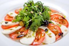 caprese沙拉 新鲜的沙拉用新鲜的水多的蕃茄用无盐干酪乳酪和新鲜的芝麻菜 库存照片