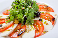 caprese沙拉 新鲜的沙拉用新鲜的水多的蕃茄用无盐干酪乳酪和新鲜的芝麻菜 免版税库存照片
