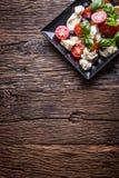 caprese салат Среднеземноморской салат Базилик и оливковое масло томатов вишни моццареллы на старой таблице дуба роскошь уклада ж Стоковые Фотографии RF