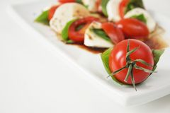 Caprese. Close up of cherry tomatoes, mozzarella and basil with olive oil and balsamic vinegar name caprese in Italy Royalty Free Stock Photography