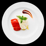 Caprese appetizer on plate isolated on black Stock Photo