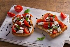 Caprese Bruschetta. Tomatoes, basil, mozzarella cheese with balsamic reduction drizzle on toast. Antipasto - starter dish Royalty Free Stock Photos