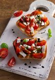 Caprese Bruschetta. Tomatoes, basil, mozzarella cheese with balsamic reduction drizzle on toast. Antipasto - starter dish Royalty Free Stock Photography
