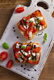 Caprese Bruschetta. Tomatoes, basil, mozzarella cheese with balsamic reduction drizzle on toast. Antipasto - starter dish. View from above, top Stock Photos