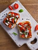 Caprese Bruschetta. Tomatoes, basil, mozzarella cheese with balsamic reduction drizzle on toast. Antipasto - starter dish. View from above, top Royalty Free Stock Photography