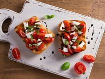 Caprese Bruschetta. Tomatoes, basil, mozzarella cheese with balsamic reduction drizzle on toast. Antipasto - starter dish. View from above, top Stock Images