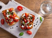 Caprese Bruschetta. Tomatoes, basil, mozzarella cheese with balsamic reduction drizzle on toast. Antipasto - starter dish. View from above, top Royalty Free Stock Image