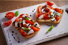 Caprese Bruschetta on white rustic chopping board. Tomatoes, basil, mozzarella cheese with balsamic sauce on toast. Antipasto - starter dish. horizontal Stock Images