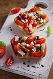 Caprese Bruschetta on white rustic chopping board. Tomatoes, basil, mozzarella cheese with balsamic sauce on toast. Antipasto - starter dish. vertical Stock Photo