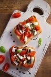 Caprese Bruschetta on white rustic chopping board. Tomatoes, basil, mozzarella cheese with balsamic sauce on toast. Antipasto - starter dish. overhead Royalty Free Stock Image