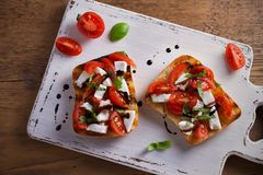 Caprese Bruschetta on white rustic chopping board. Tomatoes, basil, mozzarella cheese with balsamic sauce on toast. Antipasto - starter dish. overhead Royalty Free Stock Images