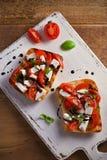 Caprese Bruschetta on white rustic chopping board. Tomatoes, basil, mozzarella cheese with balsamic sauce on toast. Antipasto - starter dish. overhead Royalty Free Stock Photos