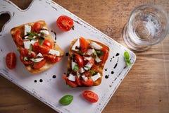 Caprese Bruschetta on white rustic chopping board. Tomatoes, basil, mozzarella cheese with balsamic sauce on toast. Antipasto - starter dish. overhead Royalty Free Stock Photo