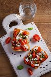 Caprese Bruschetta on white rustic chopping board. Tomatoes, basil, mozzarella cheese with balsamic sauce on toast. Antipasto - starter dish. overhead Royalty Free Stock Photography