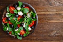 Caprese con la mozzarella, los tomates, la albahaca y las aceitunas Ensalada italiana clásica Imágenes de archivo libres de regalías