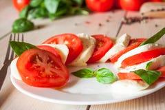 Caprese con los tomates, la mozzarella y la albahaca Fotos de archivo libres de regalías