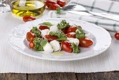 Caprese Italiaanse salade inbegrepen mozarella, tomaten, basilicum en pestosaus royalty-vrije stock foto