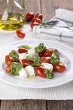 Caprese Italiaanse salade - mozarella, tomaat, basilicum, pesto stock afbeelding