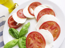 Caprese Italian Cuisine. Italian cuisine. A delicious closeup of caprese summer dish made with fresh tomato, mozarella and basil Stock Images