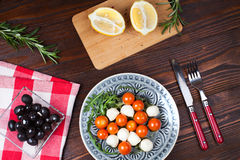 Caprese on italian table. Salad caprese made with arugula, tomatoes, cheese mozzarella balls and on plate with fork and knife, on  wooden table with olives Stock Photography