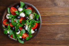 Caprese with mozzarella, tomatoes, basil and olives. Classic Italian salad. Classic Italian salad with mozzarella, tomatoes, basil, olives and olive oil royalty free stock images
