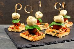 Caprese pizza skewer appetizers against a dark background. Caprese pizza skewers with mozzarella, basil, and tomatoes. Appetizers against a dark stone background stock photography