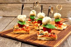 Caprese pizza skewer appetizers against a wood background. Caprese pizza skewers with mozzarella, basil, and tomatoes. Appetizers against a rustic wood stock photography