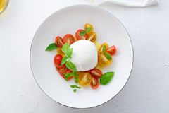 Caprese sałatka z pomidorami, mozarella, basilem i oliwa z oliwek czerwonymi i żółtymi, Zamknięty widok Białego tła odgórny widok obraz stock
