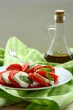 Caprese salad. On a white plate on a green background Stock Photo