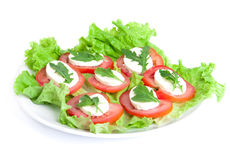 Caprese salad. Tomatoes, mozzarella and eruca on plate. Over white background Stock Photo