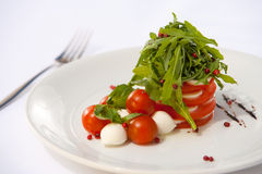 Caprese salad. A delicious italian salad with tomatoes, cherry, mazzarella, arugula and balsamic vinegar on a white plate Stock Photography