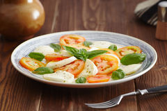Caprese salad. In a blue pastel plate on an old wooden table, with salt and pepper Royalty Free Stock Image