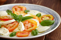 Caprese salad. In a blue pastel plate on an old wooden table, with salt and pepper Royalty Free Stock Photos
