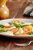 Caprese salad. In a blue pastel plate on an old wooden table, with salt and pepper stock photography