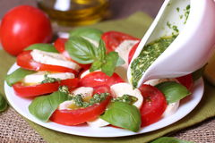 Caprese salad with ingredients like oil, tomatoes and mozzarella cheese. Italian traditional caprese salad with pesto sauce Royalty Free Stock Photos