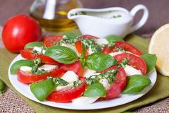 Caprese salad with ingredients like oil, tomatoes and mozzarella cheese. Italian traditional caprese salad with pesto sauce Royalty Free Stock Image