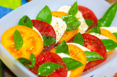 Caprese salad made of red and yellow tomatoes Royalty Free Stock Photos