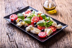 Caprese Salad.Mediterranean salad. Mozzarella cherry tomatoes basil and olive oil on old oak table. Italian cuisine Royalty Free Stock Photo