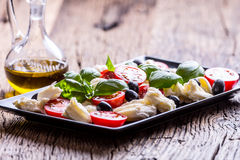 Caprese Salad.Mediterranean salad. Mozzarella cherry tomatoes basil and olive oil on old oak table. Italian cuisine Royalty Free Stock Photography