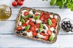 Caprese salad with mozzarella cheese ripe tomatoes olives and basil leaves. Italian or mediterranean healthy meal royalty free stock photography