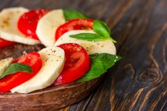 Caprese salad with mozzarella on a light wooden background, clos stock photography