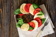 Caprese salad with mozzarella on a light wooden background, top royalty free stock photos