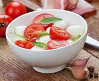 Caprese salad with mozzarella, tomato, basil on white plate Stock Photos