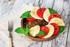 Caprese salad with mozzarella on white wooden background stock photos