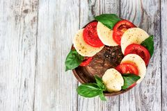 Caprese salad with mozzarella on white wooden background, top vi royalty free stock images